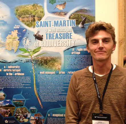 Julien Chalifour at the GCFI conference, in front of the poster featuring the 818 species in Saint-Martin